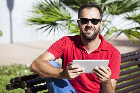 Man using a tablet sitting on a bench. He is looking at camera.