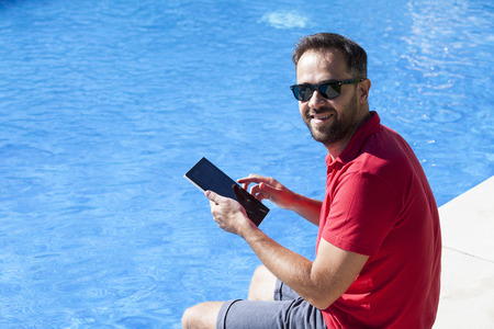 Man using a tablet at the poolside. Banco de Imagens
