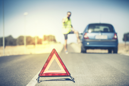 Emergency triangle. Man talking by phone and stopped car in the background.