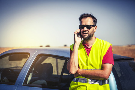 emergency call: Man talking by phone and waiting for assistance after car breakdown.