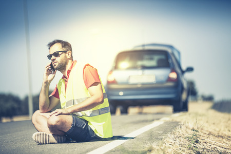 warning vest: Man sitting on the road talking by phone after a car breakdown.