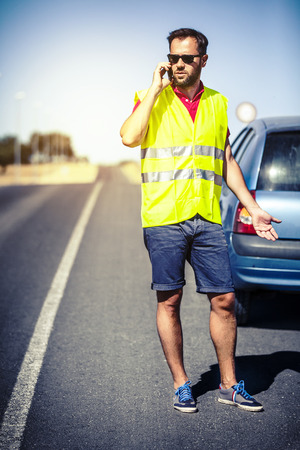 security vest: Stressed man talking by phone after car failure. Stock Photo