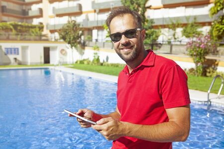 Man using a tablet at the poolside. 版權商用圖片