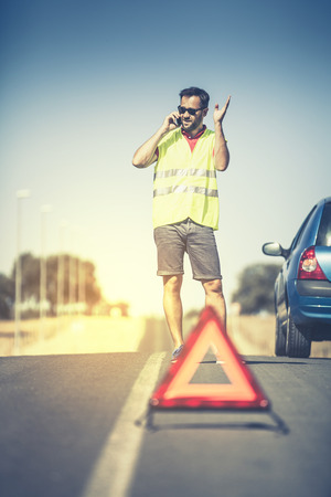 warning vest: Angry man discussing with assistance company by phone after car breakdown.