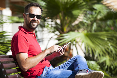 uomo rosso: Man using a tablet sitting in a bench. He is looking at camera.