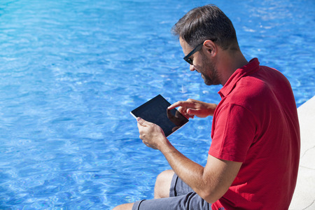 poolside: Man using a tablet at the poolside. Stock Photo