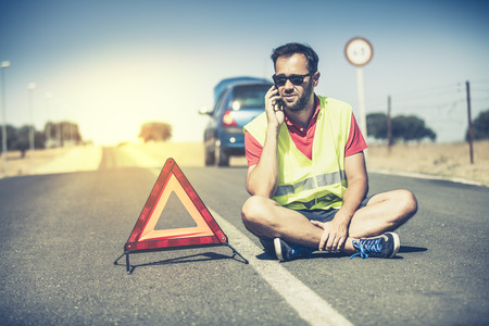 car service: Man sitting on the asphalt in the middle of the road. He is talking to the assistance by phone. Stock Photo
