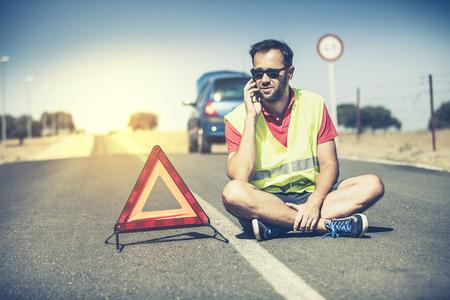 Man zit op het asfalt in het midden van de weg. Hij is in gesprek met de hulp via de telefoon. Stockfoto