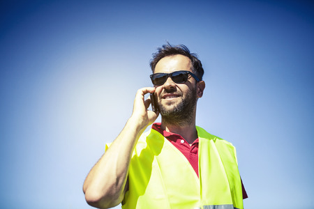 Engineer with reflective vest and sunglasses talking by phone. Blue sky background.