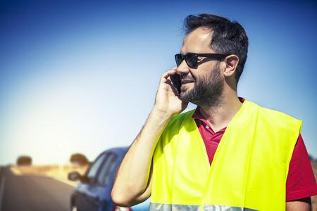 emergency vest: Smiling man talking by phone after car breakdown.