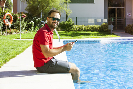 Man sitting at the poolside using a tablet