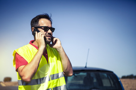warning vest: Man talking to insurance company by phone after car breakdown.