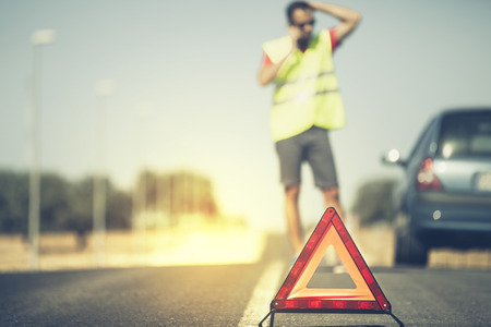 damaged car: Emergency triangle with man and stopped car in the background. Vintage style.