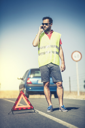 warning vest: Man talking by phone in the middle of the road. Car insurance concept. Stock Photo