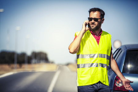 warning vest: Stressed man talking by phone after car breakdown Stock Photo