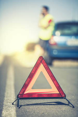 Emergency triangle. Man and stopped car in the background. Vintage style.