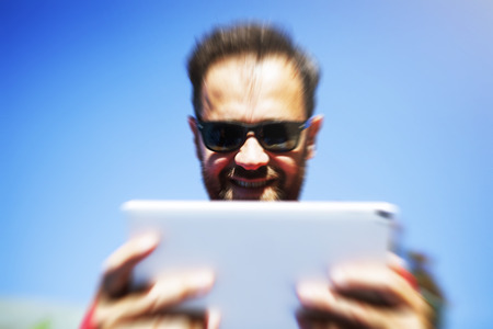Close up portrait of man reading a tablet. Fast internet connection concept. Zoom effect.