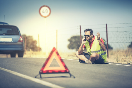 emergency vest: Angry man talking to insurance company by phone after car breakdown. Stock Photo