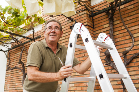 Smiling senior man climbing a ladder.