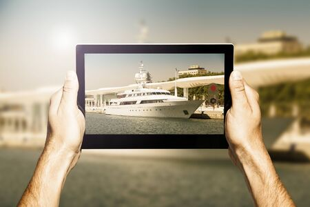 taking photo: Taking photo with a tablet. Yacht on the scene. Stock Photo