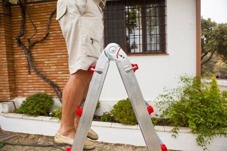 Senior man legs on a ladder step.