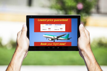 Last minute flights on tablet holded by hands. 스톡 사진