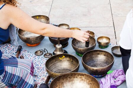 sound healing: Tibetan bowls playing during yoga and meditation session.