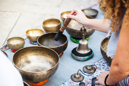 Detail of tibetan bowls playing during meditation session.