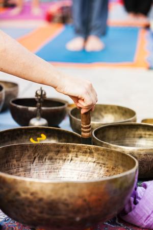 Detail van Tibetaanse klankschalen spelen tijdens yoga-sessie.