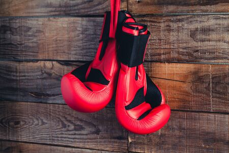 Two red boxing gloves in a wooden background wall.