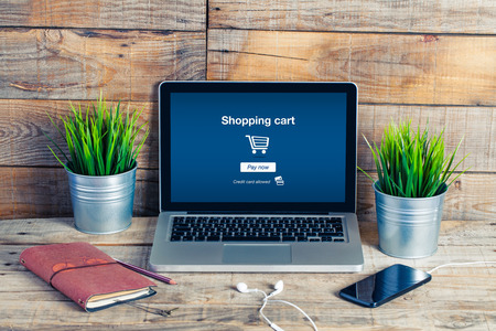 Shopping cart website template in a laptop screen. Close up of wooden desk.