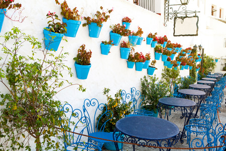 flowerpots: Tables and chairs in a typical street of Andalusia, Spain. Stock Photo