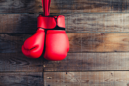 boxing knockout: Pair of red boxing gloves. Wooden wall background. Stock Photo