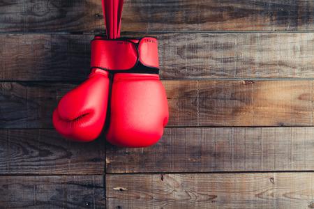 guantes: Un par de guantes de boxeo rojos. Fondo de la pared de madera. Foto de archivo
