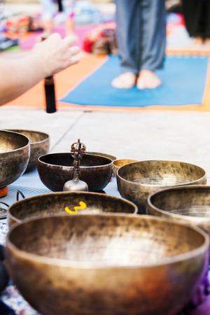 sound healing: Tibetan bowls playing during a yoga session. Stock Photo