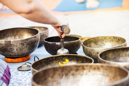 sound healing: Detail of tibetan bowls being played during meditation and yoga session. Stock Photo