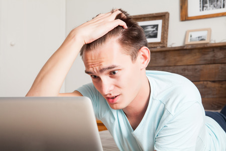Young man with the hand in the hair in front of the laptop. Stress concept.
