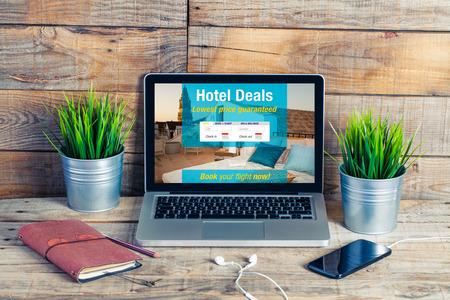 노트북 화면의 호텔 예약 웹 사이트 템플릿. 나무 책상에 컴퓨터.