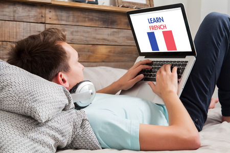 languages: Young man using a laptop for learning french while lying in the bed at home. Stock Photo