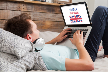 Young man using a laptop for learning english while lying in the bed at home. Archivio Fotografico