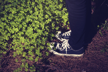 Feet in sneakers in the forest.