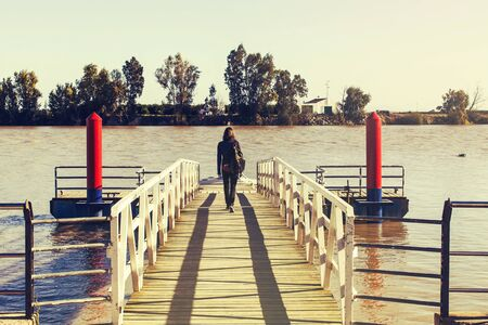 Woman in a wooden pier close to the river. 스톡 사진