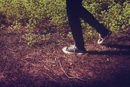 old shoes: Feet in sneakers walking in the forest. Stock Photo