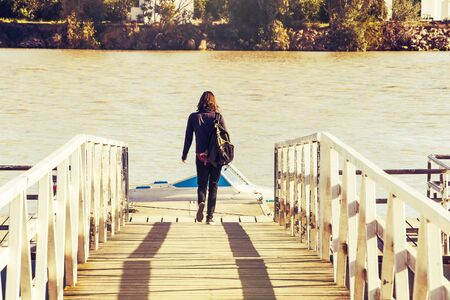 pier: Woman on a wooden pier close to the river.