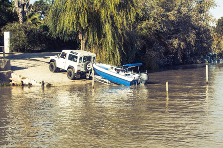 Off road vehicle towing a boat into the river.