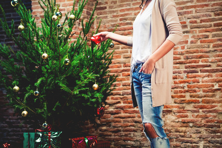 decorating: Woman placing ornaments in a Christmas tree in the background.