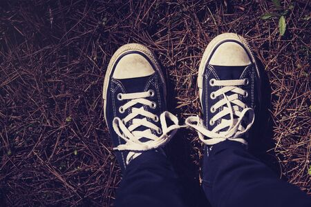 pine forest: Top view of black sneakers shoes. Vintage tone.