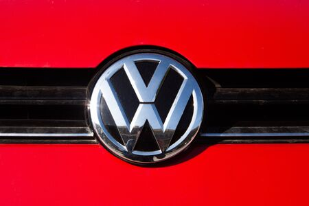 emissions: MALAGA, SPAIN - DECEMBER 2, 2015: Volkswagen car front logo over red paint in a car. Close up detail of Volkswagen brand logo in a car. Volkswagen Group cars are involved in a violation of the CO2 emissions law through an illegal software. Editorial