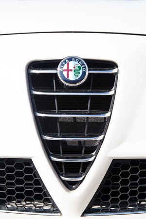alfa: MALAGA, SPAIN - DECEMBER 2, 2015: Alfa Romeo car logo in the front of car grid. Close up detail of Alfa Romeo brand logo in a car grid. Alfa Romeo Automobiles S.p.A. is an Italian car manufacturer, famous because of the beautiful designs of cars.