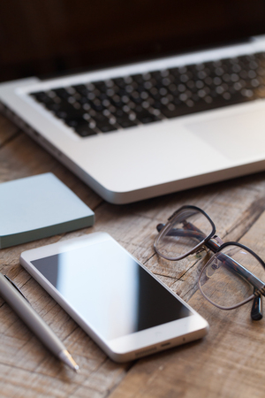 Smartphone, glasses, pen and computer over wooden table desk. Stock Photo